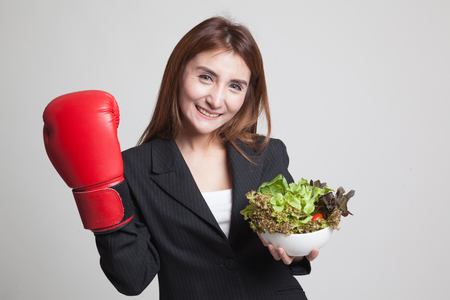 Young Asian woman with boxing glove and salad on gray background