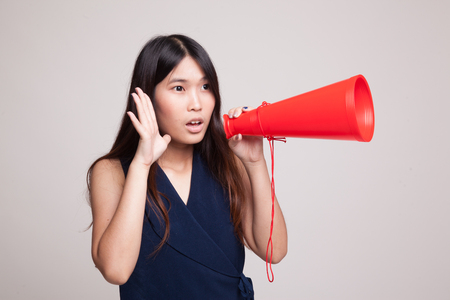 Beautiful young Asian woman announce with megaphone on gray background