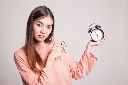 clock: Angry young Asian woman point to a clock on gray background