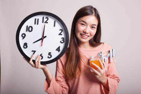 clock: Asian woman with a clock drink orange juice on gray background