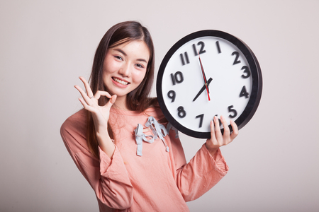 clock: Young Asian woman show OK with a clock on gray background Stock Photo