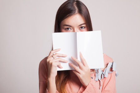 onderwijs: Young Asian woman with a book on gray background