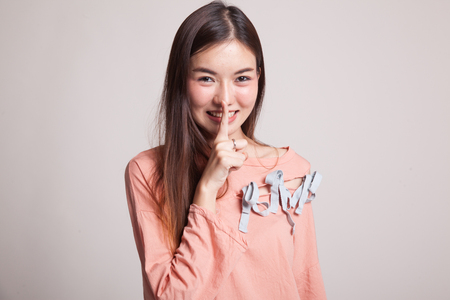 Asian girl smile show quite hand sign on gray background