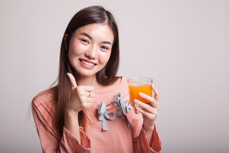 Young Asian woman thumbs up drink orange juice on gray background