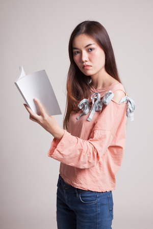 onderwijs: Young Asian woman read a book on gray background