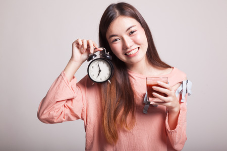 clock: Young Asian woman with tomato juice and clock on gray background Stock Photo