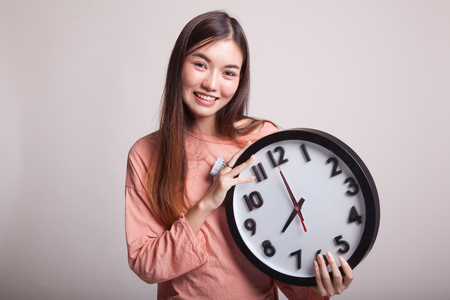 clock: Young Asian woman with a clock on gray background