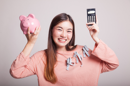 onderwijs: Asian woman with calculator and piggy bank on gray background