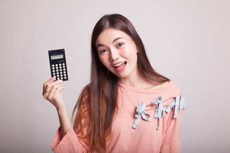 onderwijs: Asian woman smile with calculator on gray background