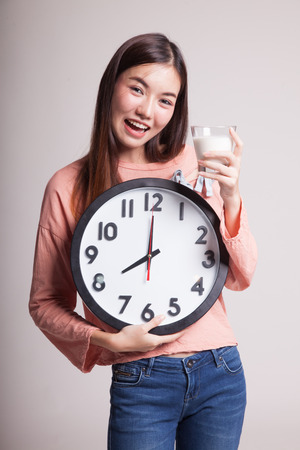 clock: Healthy Asian woman drinking  glass of milk hold clock on gray background