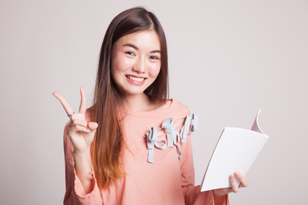 onderwijs: Young Asian woman show victor sign with a book on gray background Stockfoto