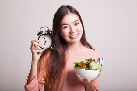 clock: Young Asian woman with clock and salad on gray background