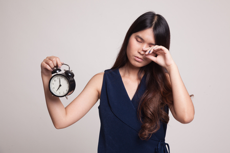 tired: Sleepy young Asian woman with a clock in the morning on gray background Stock Photo