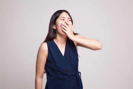 tired: Sleepy young Asian woman yawn on gray background