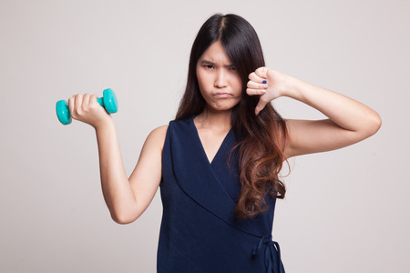 tired: Unhappy Asian woman thumbs down with dumbbells on gray background