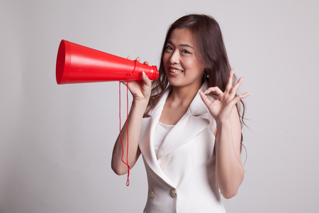 Beautiful young Asian woman show OK  announce with megaphone on gray background Stock Photo