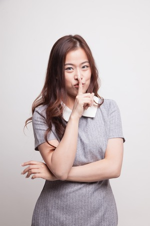quite: Asian girl smile show quite hand sign on gray background