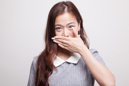Young Asian woman close her mouth with hand on gray background Stock Photo