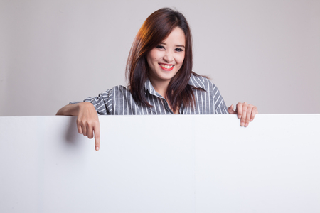 Young Asian woman point to a  blank sign on gray background