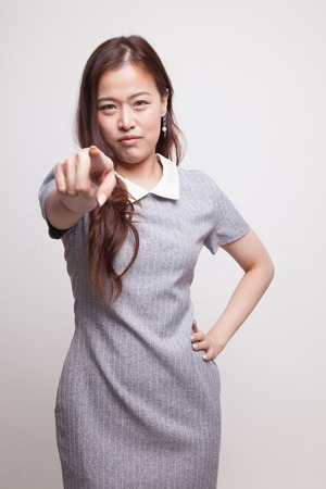 Young Asian woman angry and point to camera on gray background