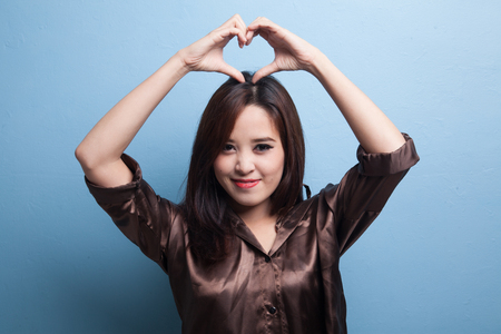 Young Asian woman gesturing heart hand sign on blue background Reklamní fotografie