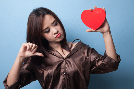Asian woman thumbs down with red heart on blue background
