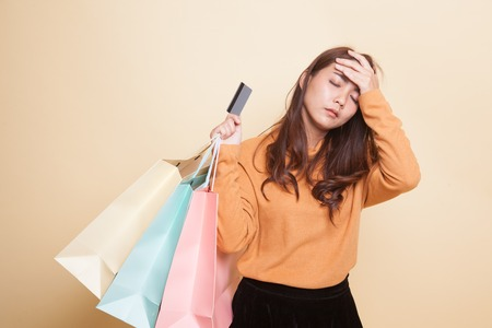 Unhappy  young Asian woman with shopping bags and credit card on beige background 스톡 콘텐츠