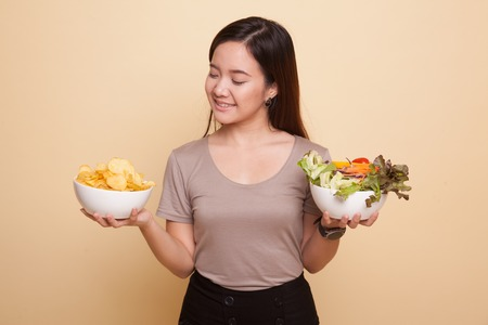 Young Asian woman with potato chips and salad on beige background Archivio Fotografico