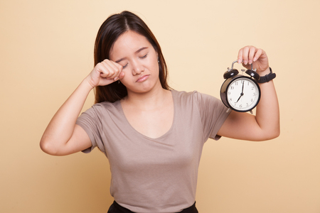 Sleepy young Asian woman with a clock in the morning on beige background