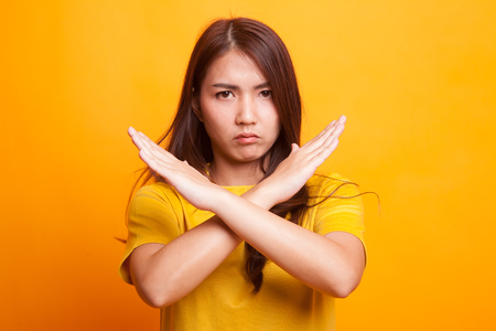 Beautiful young Asian woman say no in yellow dress on yellow background 스톡 콘텐츠