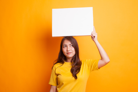 Young Asian woman with white blank sign in yellow dress on yellow background
