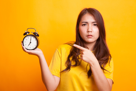 Angry young Asian woman point to a clock in yellow dess on yellow background
