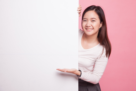 Young Asian woman present blank sign with palm hand on pink background 版權商用圖片 - 96889803