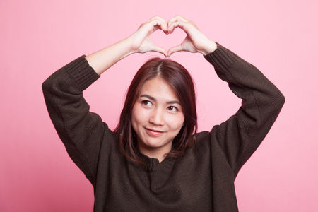 Young Asian woman gesturing heart hand sign on pink background