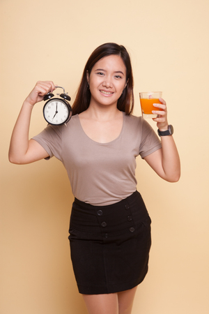 Asian woman with a clock drink orange juice on beige background Banque d'images