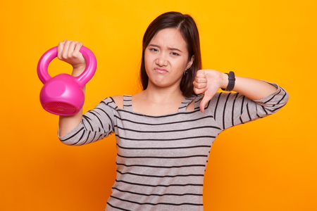 Unhappy Asian woman thumbs down with dumbbells on yellow background