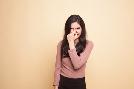 Young Asian woman  holding her nose because of a bad smell on beige background