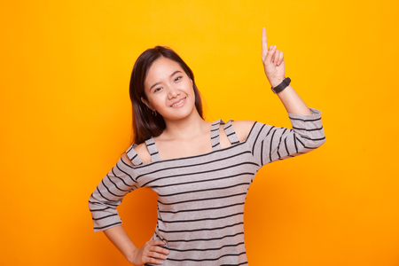 Young Asian woman smile and point up on yellow background