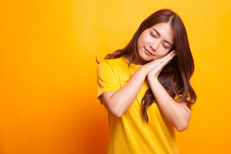 Beautiful young Asian woman with sleeping gesture in yellow dress on yellow background