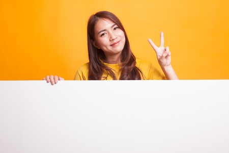 Young Asian woman show victory sign with blank sign in yellow dress on yellow background