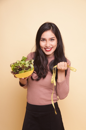 Healthy  Asian woman with measuring tape and salad on beige background