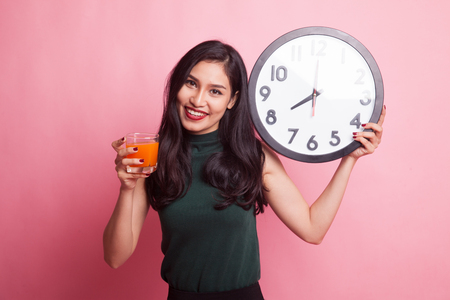 Asian woman with a clock drink orange juice on pink background