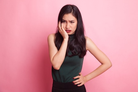 Young Asian woman got toothache on pink background Фото со стока
