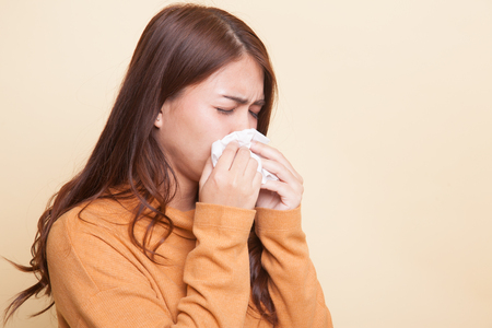Young Asian woman got sick and flu on beige background