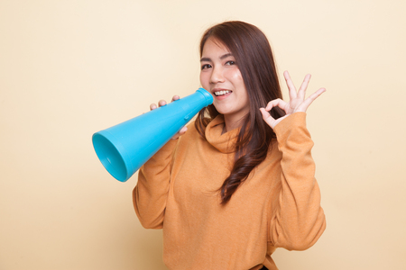 Beautiful young Asian woman show OK  announce with megaphone on beige background