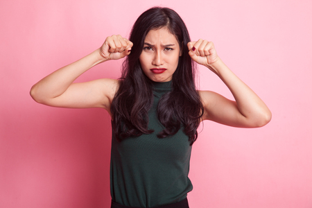 Young Asian woman sad and cry on pink background Stock Photo