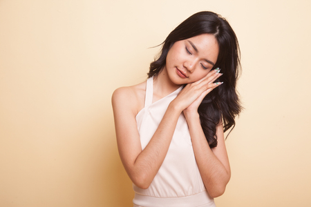 Beautiful young Asian woman with sleeping gesture  on beige background Stock Photo