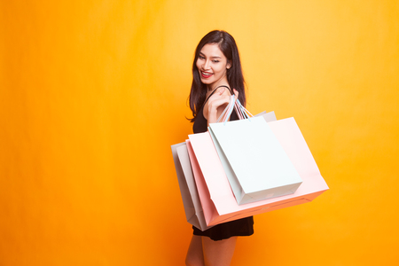 Young Asian woman happy with shopping bag on yellow background