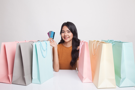 Young Asian woman with shopping bag and blank card on white background 免版税图像