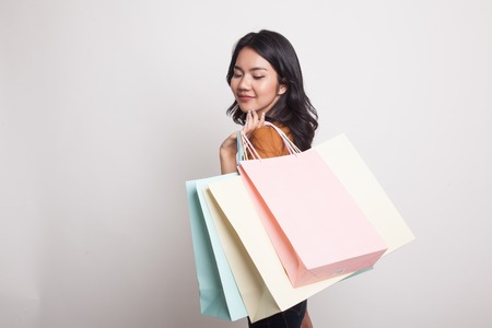 Young Asian woman happy with shopping bag on white background